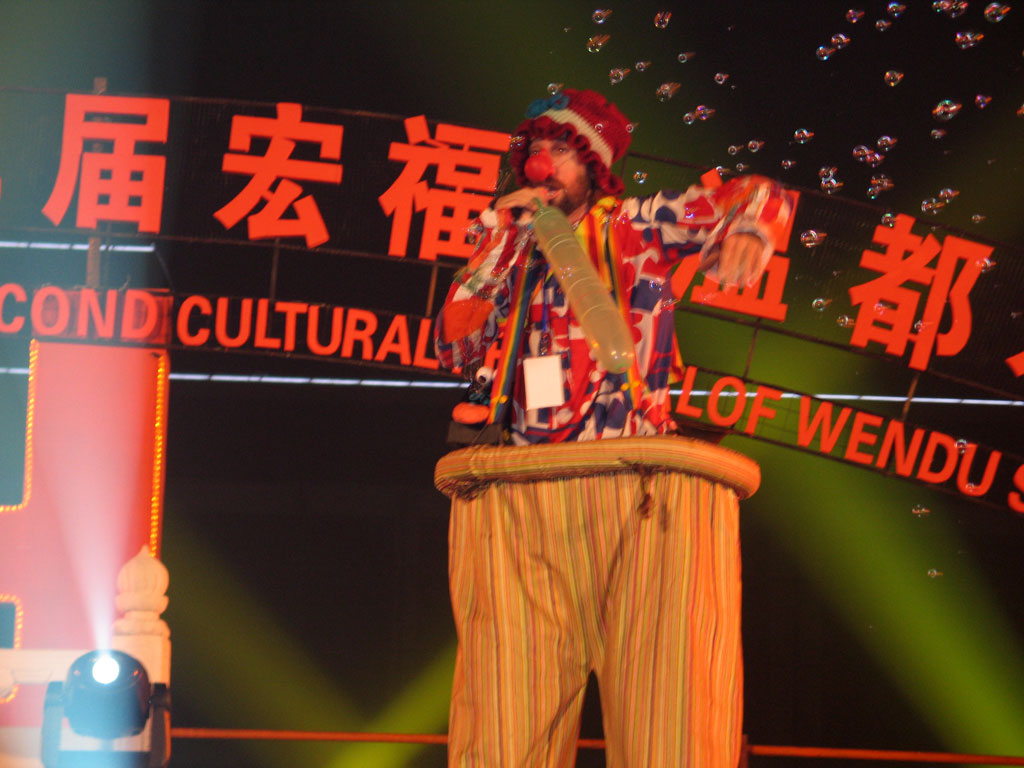 joel fox hobo clown in china on stilts blowing up a baloon